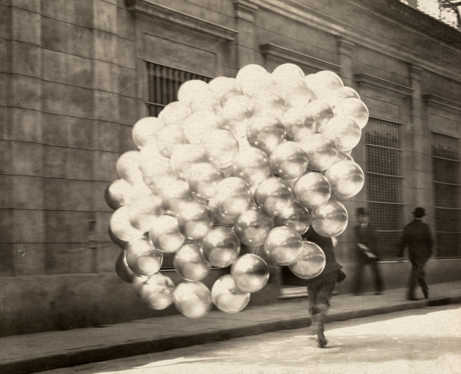 21 A balloon vendor runs across a road with a trailing mass of balloons in Buenos Aires, November 1921
