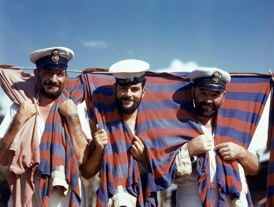 42 Three British sailors drape themselves with their soccer jerseys in Trinidad
